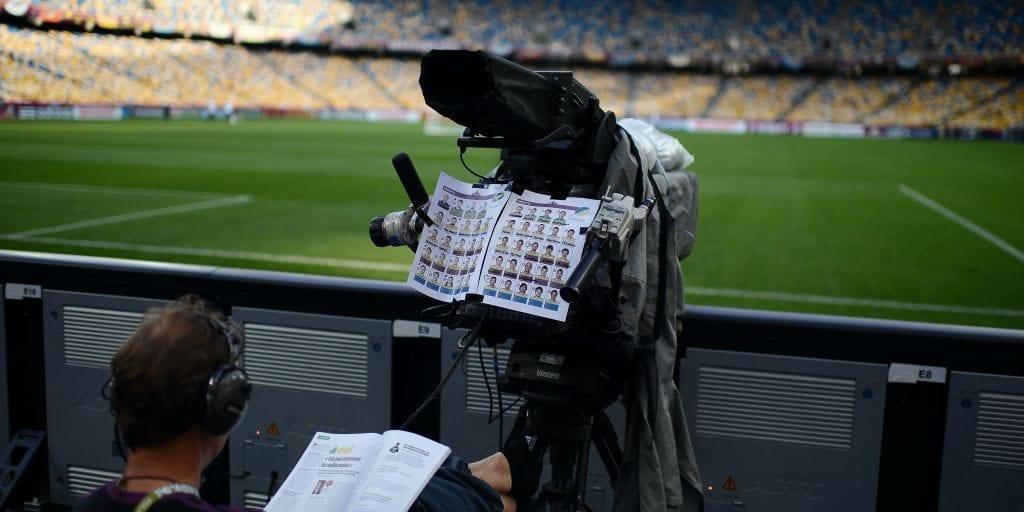 Un camarógrafo lee una revista detrás de su cámara de video en el Estadio Olímpico de Kiev
