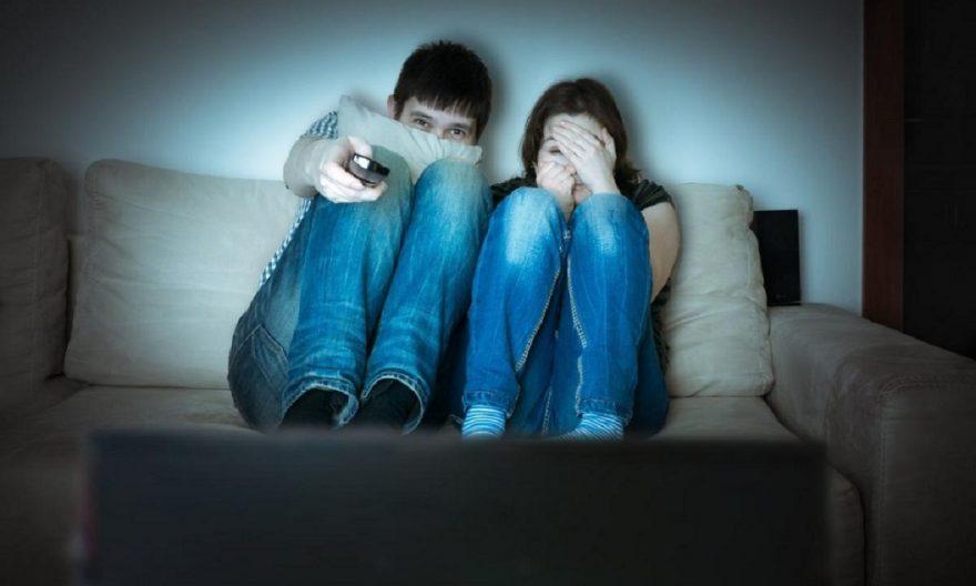 Chicos asustados frente al televisor