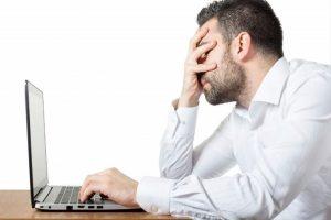 Hombre frente a su ordenador lento