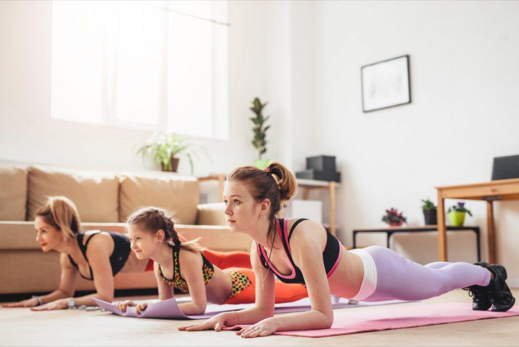 Chicas haciendo ejercicio en casa y en familia