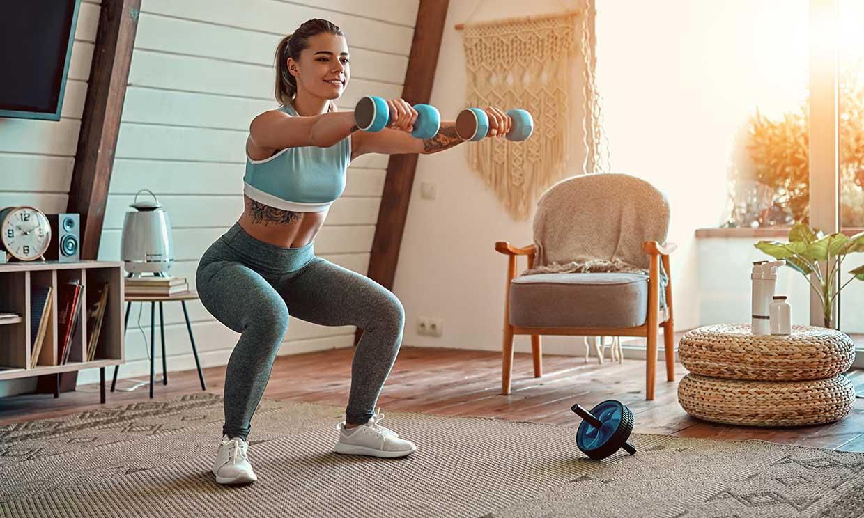 Mujer joven haciendo ejercicios en casa durante la cuarentena