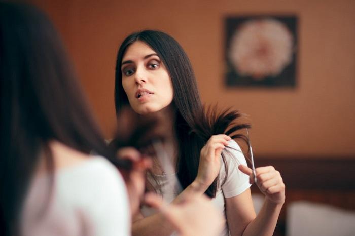 mujer cortándose el cabello frente a un espejo