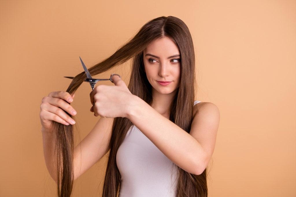 Mujer cortando su propio cabello