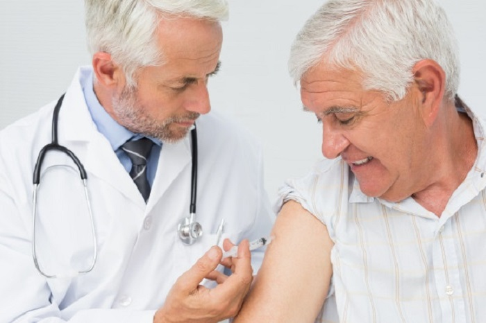 Doctor inyectando a un hombre