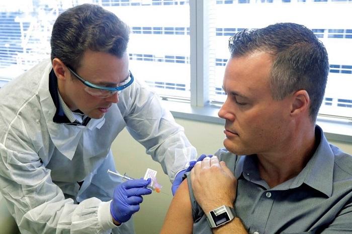 Doctor inyectando a un hombre adulto en el brazo