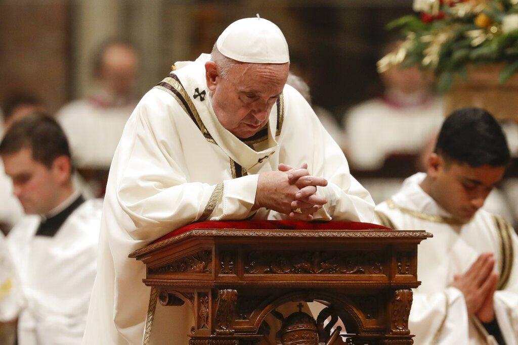 El papa Francisco ora durante la misa de Nochebuena vestido de blanco con sus manos entrelazadas sobre un púlpito