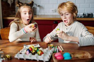 Dos niños decorando los huevos de pascua