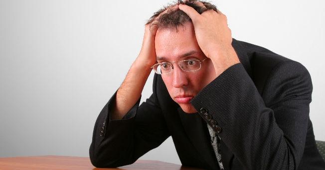 hombre de estados unido vestido de negro con sus manos en la cabeza en la cabeza y su rostro en pànico