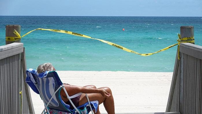 Mujer tomando sol en una playa cerrada y desierta