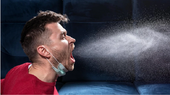 Hombre estornudando y expulsando secreciones al ambiente